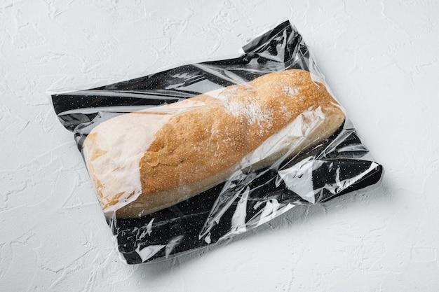 Pão de ciabatta integral artesanal recém-assado em uma sacola de mercado, na mesa branca
