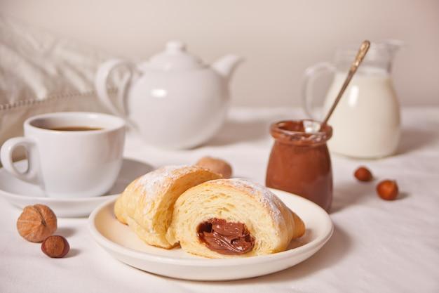 Pão de croissants frescos com chocolate no prato, xícara de café, jarra de leite