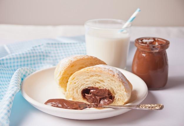 Pão de croissants frescos com chocolate no prato, xícara de café, pote de leite nas proximidades em branco