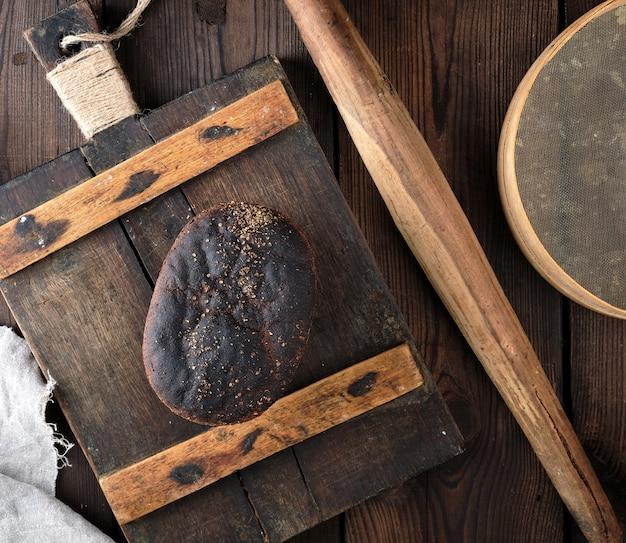 Pão de farinha de centeio cozido em uma placa de madeira vintage muito antiga