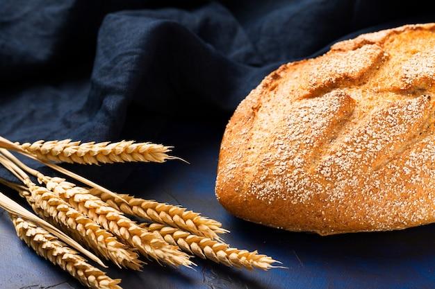 Pão de fermento integral com orelhas de cereais e guardanapo em azul escuro