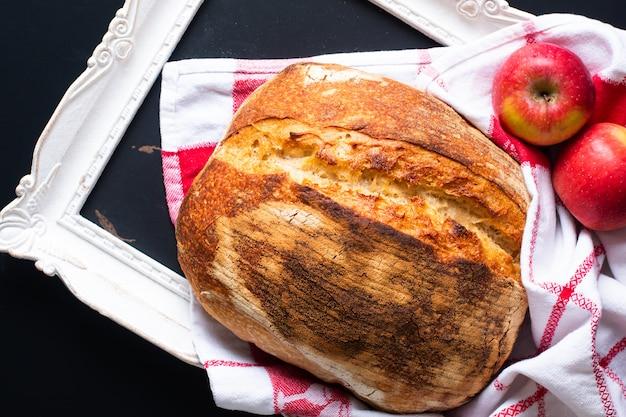 Pão de fermento rústico orgânico artesão com maçãs em um quadro