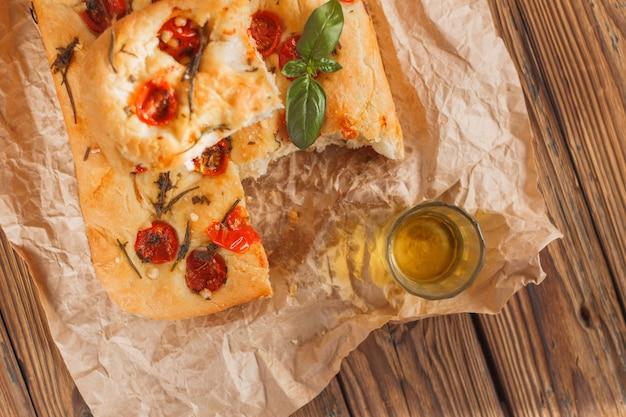 Pão de focaccia com tomate e alecrim manjericão na madeira no papel marrom bege