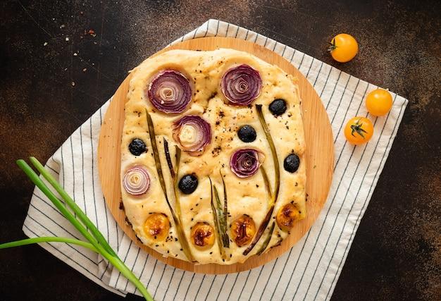 Pão de focaccia italiana com vegetais e ervas em toalha de mesa listrada focaccia de jardim