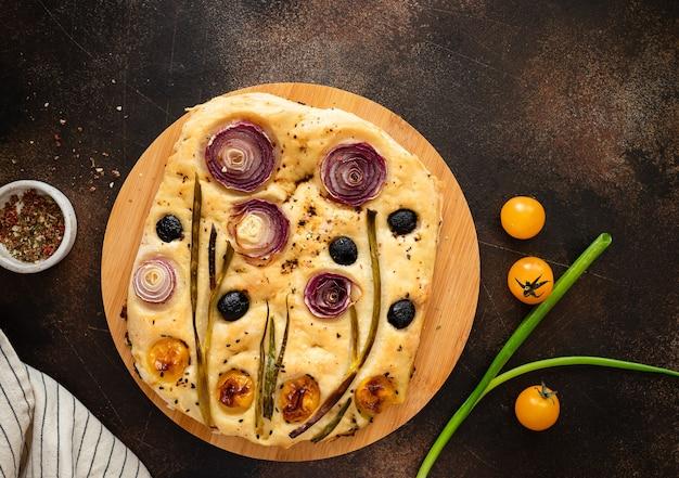 Pão de focaccia italiana com vegetais e ervas em uma tábua de cortar focaccia de jardim
