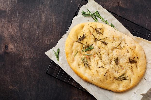 Pão de focaccia tradicional italiana assando com temperos aromáticos e alecrim no fundo da mesa rústica de madeira velha. vista do topo.