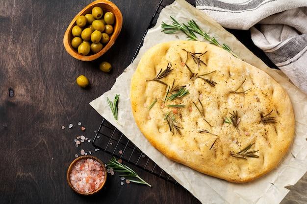 Pão de focaccia tradicional italiana assando com temperos aromáticos e alecrim no fundo da mesa rústica de madeira velha. vista do topo
