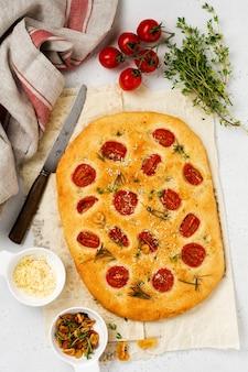 Pão de focaccia tradicional italiana assando com tomate cereja, parmesão e alecrim em fundo marrom claro. vista do topo.