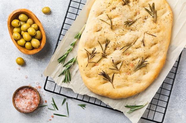 Pão de focaccia tradicional italiana recém-assada assada com temperos e alecrim em papel vegetal e parede cinza claro. vista do topo.