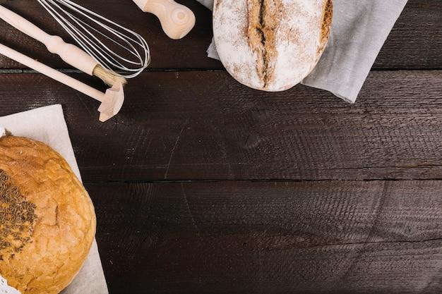 Pão de forma em papel de tecido com equipamentos de cozinha no fundo escuro de madeira