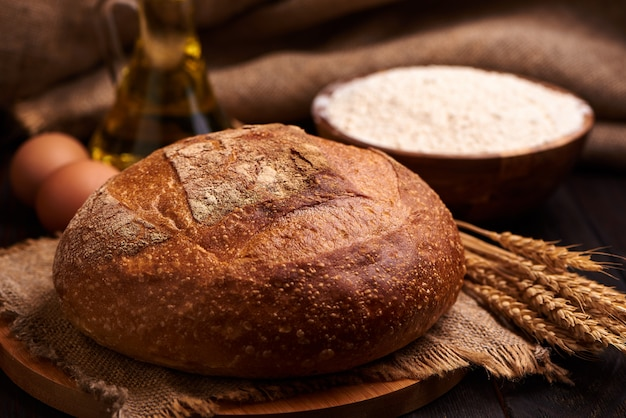 Pão de forma sobre uma superfície de madeira com farinha, óleo vegetal com ovos