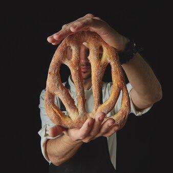 Pão de fougas caseiro nas mãos de um padeiro