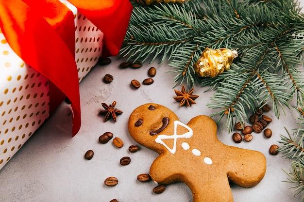 Pão de gengibre de natal, grãos de café, ramo de abeto e caixa presente no chão cinza