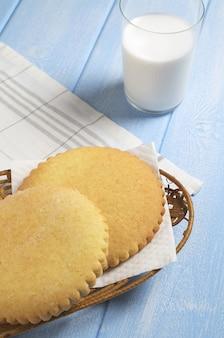 Pão de gengibre e copo de leite no café da manhã na mesa de madeira azul