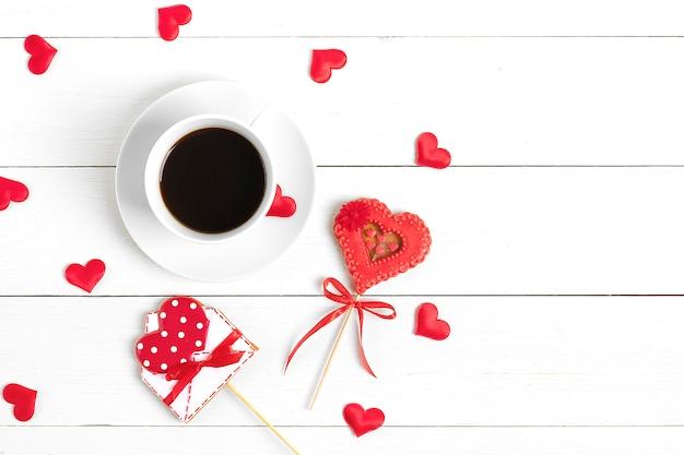 Pão de gengibre em forma de coração vermelho e envelope para escrever, café em fundo branco de madeira