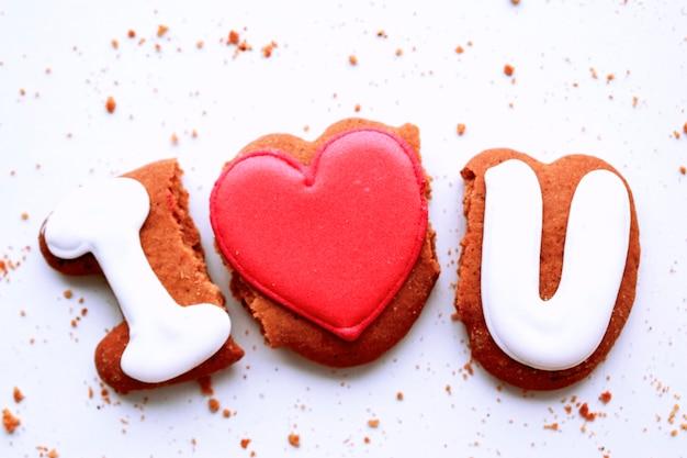 Pão de gengibre na forma de inscrições eu amo (coração) você, as migalhas do pão de gengibre, a composição é apresentada