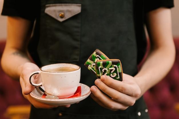 Pão de gengibre para um homem até 23 de fevereiro e uma xícara de café nas mãos de um garçom, foco seletivo