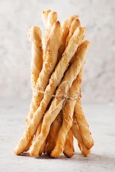 Pão de grissini italiano com sementes de gergelim em fundo claro, foco seletivo, orientação vertical