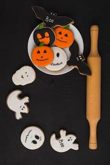 Pão de halloween na placa perto de biscoitos e êmbolo