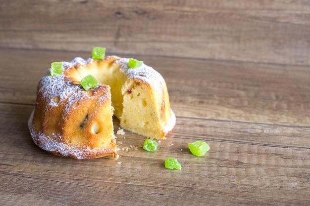 Pão de ló com maçãs e açúcar em pó no fundo de madeira