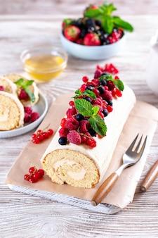 Pão de ló, creme de enchimento e frutas, morango, framboesa, mirtilo e groselha em fundo branco de madeira. foco suave. conceito de comida de verão