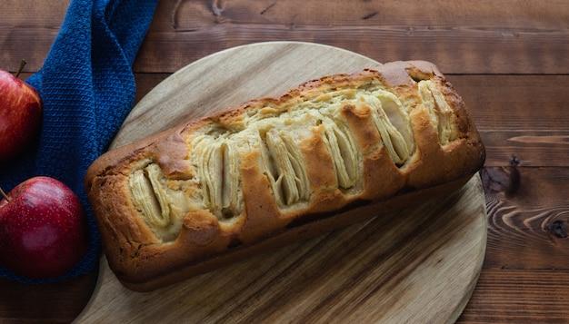Pão de ló de apple em uma placa de cozinha em uma mesa de madeira escura. copie o espaço. conceito de cozimento.