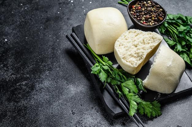Pão de lótus chinês do steam fundo preto. vista do topo. copie o espaço.