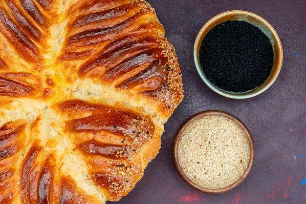 Pão de massa assada com arroz cru em fundo escuro.