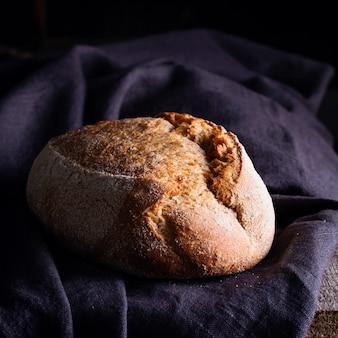Pão de massa azeda caseiro acabado de cozer num guardanapo de linho escuro, de madeira.