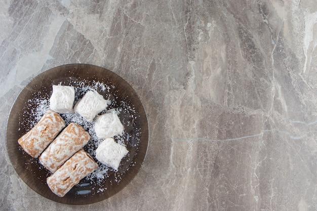 Pão de mel com geléia em esmalte de açúcar e balas de algodão em um prato de mármore.