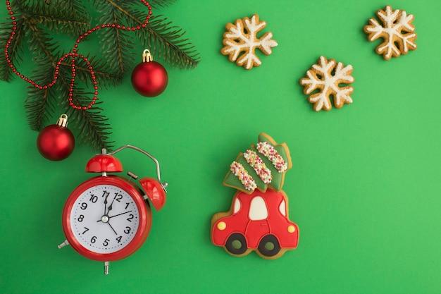 Pão de mel de natal em forma de carro, floco de neve, abeto e despertador vermelho sobre fundo verde. vista do topo. copie o espaço.