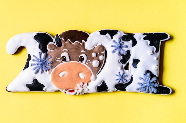Pão de mel de natal em forma de touro em fundo amarelo, plano leigo, close-up.