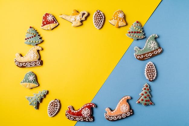 Pão de mel de natal em fundo amarelo e azul. floco de neve, abeto, estrela, trenó, cones, cone, estrela, forma de sino.