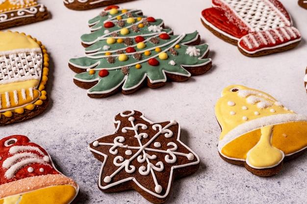 Pão de mel de natal em fundo cinza de concreto. fechar-se. floco de neve, abeto, estrela, trenó, cones, cone, estrela, forma de sino.