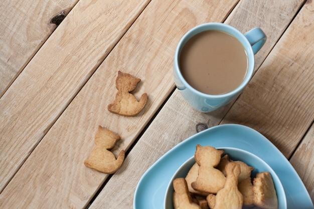 Pão de mel delicioso cozido em um prato azul, uma xícara de café de leite para uma mesa de madeira clara.