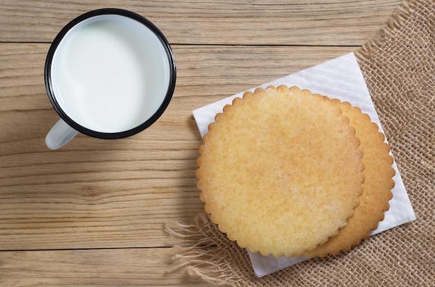 Pão de mel e xícara de leite no café da manhã na mesa de madeira, vista superior