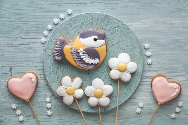 Pão de mel em forma de pássaro chapim, corações e flores em madeira com textura clara