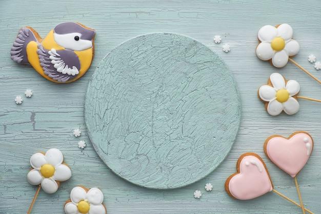 Pão de mel em forma de um pássaro chapim, corações e flores na placa de madeira cinza