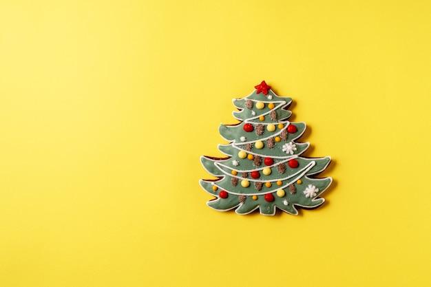 Pão de mel festivo de natal e ano novo em forma de árvore do abeto em fundo amarelo, copie o espaço