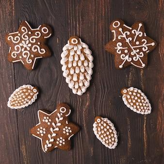 Pão de mel festivo de natal e ano novo em forma de cones e estrelas planas sobre um fundo marrom de madeira.