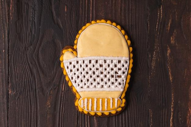 Pão de mel festivo de natal e ano novo em forma de luva, plana leiga, sobre fundo marrom de madeira.