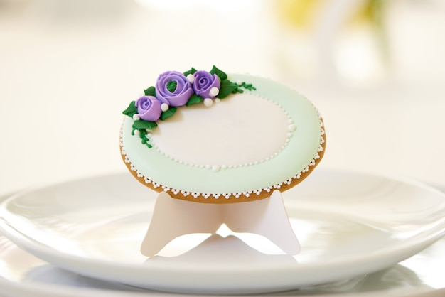 Pão de mel redondo, coberto com esmalte branco e decorado com carrinhos de flores violetas e padrão nos pratos, perto de uma taça de vinho em uma mesa de casamento festiva. foto foi feita