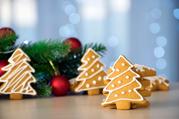 Pão de mel tradicional em forma de árvore de natal com glacê branco e ramos de abeto, brinquedos vermelhos e luzes de bokeh no fundo