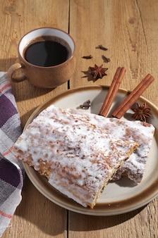 Pão de mel vitrificado com passas e xícara de café em fundo de madeira