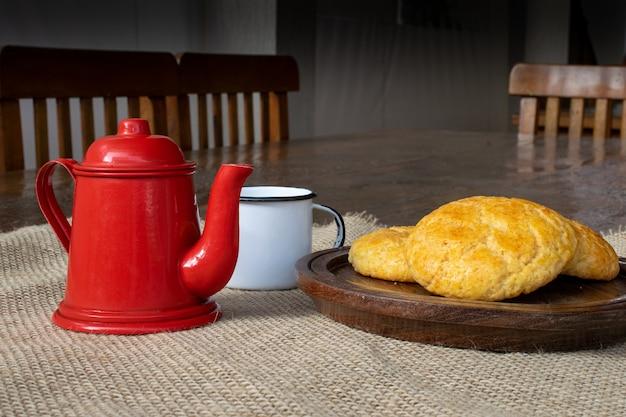 Pão de milho na placa de madeira, com bule vermelho e xícara branca na mesa