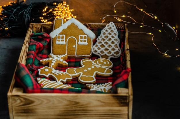 Pão de natal com açúcar de confeiteiro branco pintado sobre um fundo escuro.