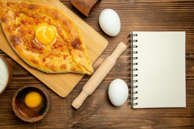 Pão de ovo delicioso assado com produtos em uma mesa de madeira marrom pão de ovo assado de cima