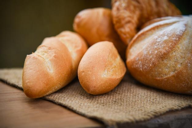 Pão de padaria fresco vários tipos de saco na mesa rústica comida de pequeno-almoço caseiro