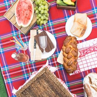 Pão de pão trançado acabado de cozer; frutas e pão na toalha de mesa quadriculada