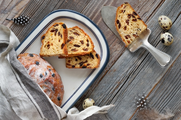 Pão de páscoa (osterbrot em alemão). vista superior do pão frutado tradicional em madeira rústica com folhas frescas e ovos de codorna